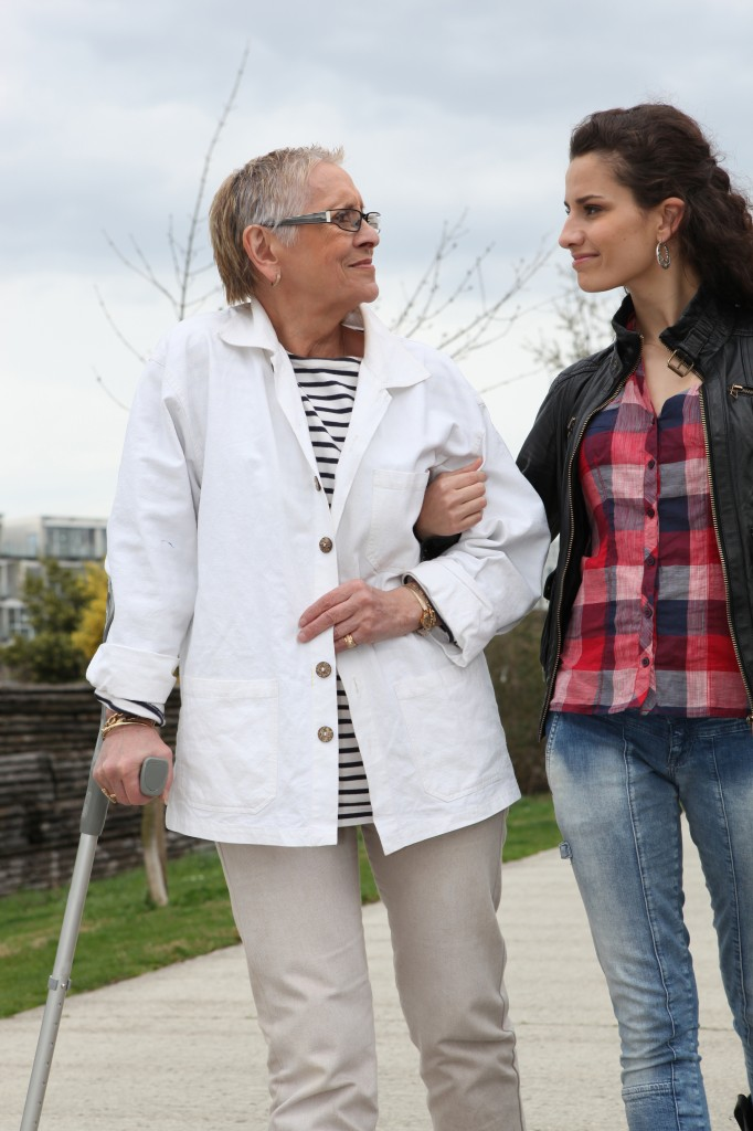 Young woman helping elderly person to walk with a crutch