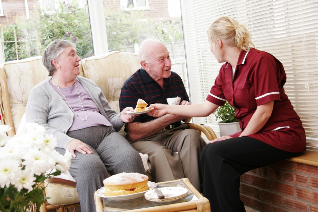 elderly couple and care worker enjoying a tea break